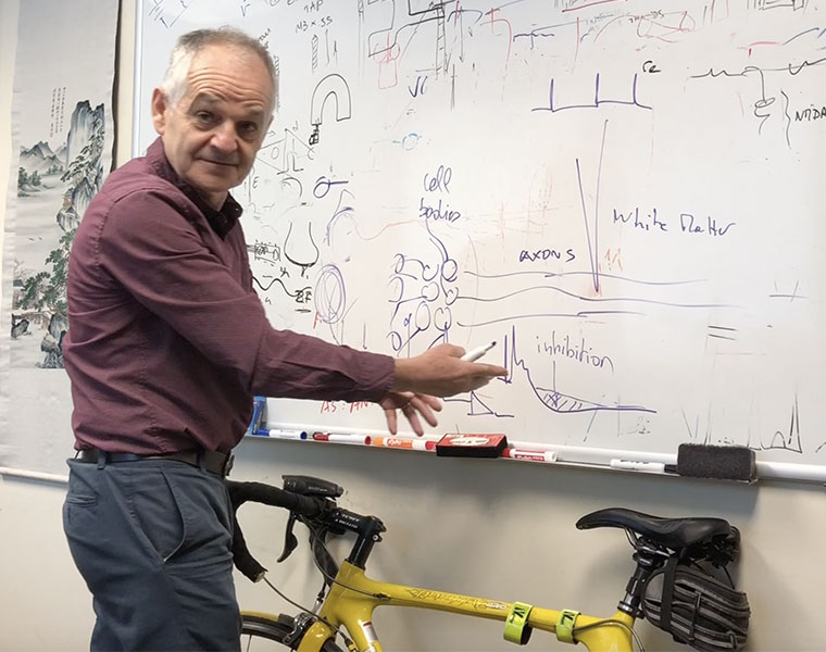 Professor Dominique Durand stands at a white board in his office