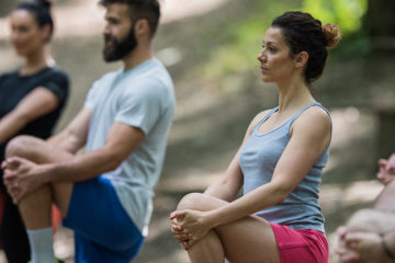Photo of a group of people doing a stretching exercise outdoors