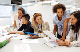 Photo of a group of students gathered around a table with papers meeting with a mentor
