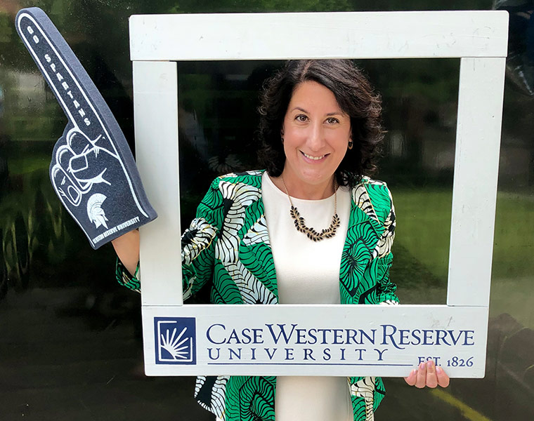 "Photo of Suzanne Rivera with a CWRU foam finger on and holding a photo frame that says ""Case Western Reserve University"""