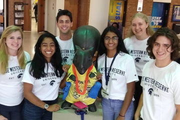Photo of six CWRU students posing with a squirrel statue during Entrepreneurship Immersion Week