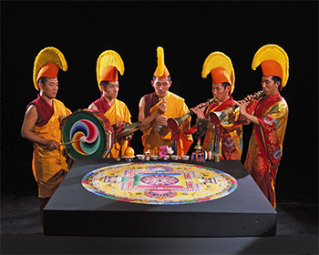 Tibetan monks playing instruments around a sand mandala