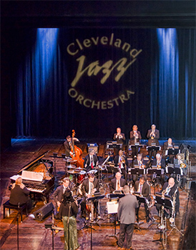 A large assemblage of jazz musicians playing on stage