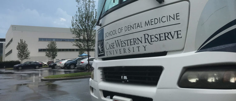 front end of the dental van at Case Western Reserve University, with the School of Dental Medicine in the background.