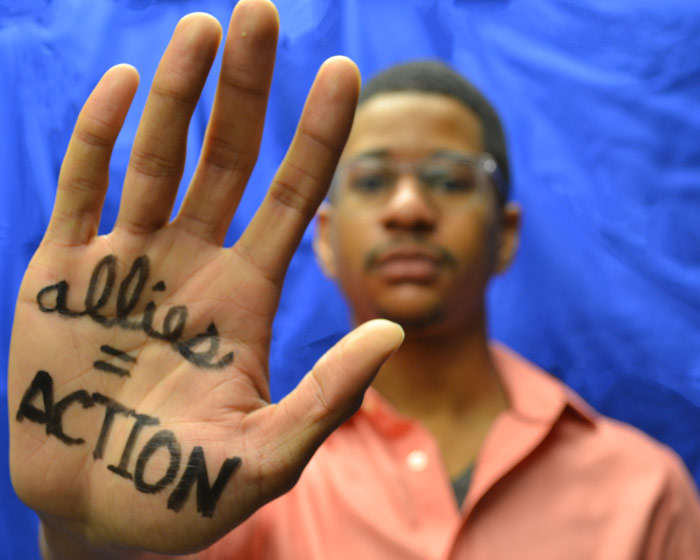 "Photo of Richard McGuire with his ""allies = actions"" written on his outstretched hand"