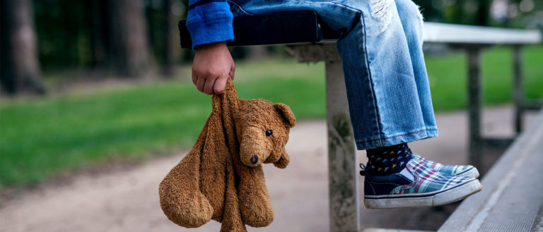 Young boy holding teddybear while alone on the bleachers