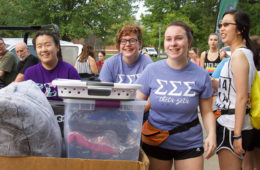 Three Case Western Reserve University students smiling as they move boxes on move-in day