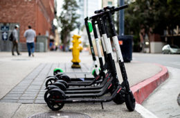Photo of dockless, electric scooters lined up on the sidewalk