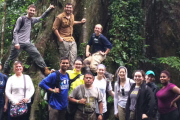 A group of students pose for a photo in the rainforest on a trip to Ecuador