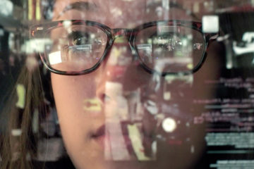 Female with glasses looking through a screen of data