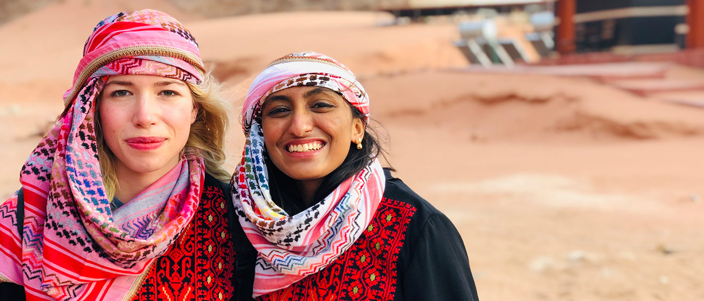 Photo of two female students posing for photo in the Wadi Rum desert of Jordan