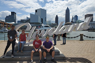 Four members of the Class of 2023 pose with the Cleveland sign with the Rock and Roll Hall of Fame and skyline in the background