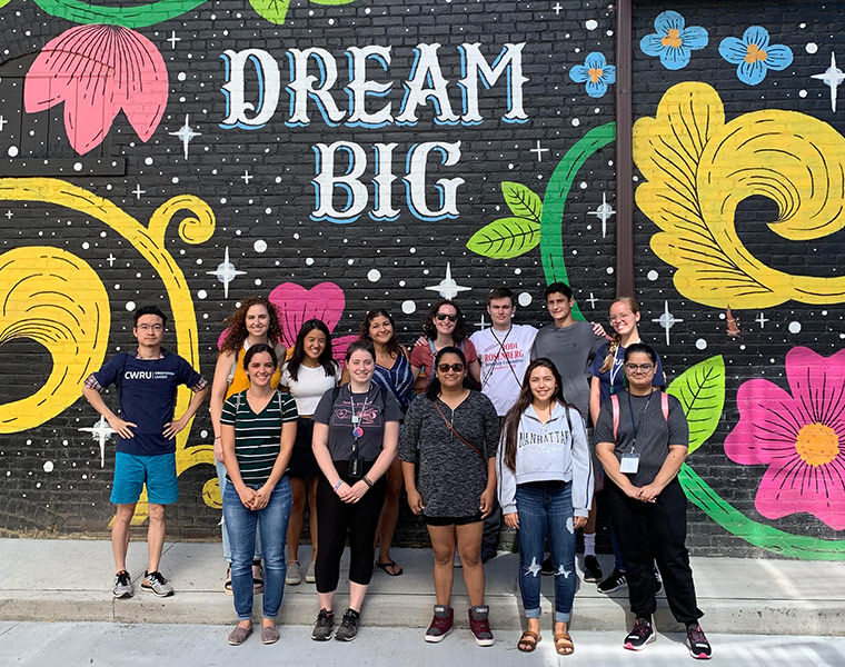 "Photo of students standing in front of a mural that says ""Dream big"""
