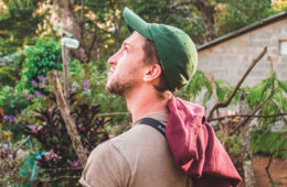 Student Michael Douglass wearing a green ball cap and looking up toward the sky in the Dominican Republic