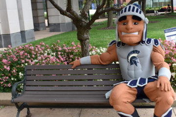 Photo of Spartie sitting on a bench near Kelvin Smith Library