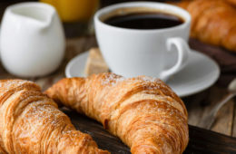 Photo showing two croissants and a cup of coffee