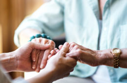 photo of a health care worker or volunteer holding the hands of an elderly person