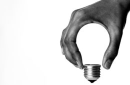 A hand making a lightbulb shape using the base of a lightbulb