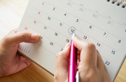 Close up photo of someone circling a date on a calendar