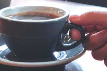 Close up photo of someone's hand picking up a coffee cup