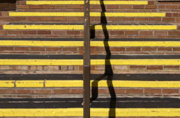 Photo of brick stairs with black and yellow markings and a railing