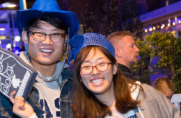Two students pose for a photo at the Blue Block party with one holding a foam finger