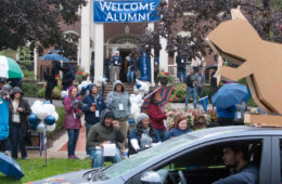 Photo of a car with a cardboard squirrel driving by the Linsalata Alumni Center during the homecomeing parade as an audience looks on