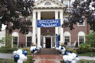 "Photo of the Linsalata Alumni Center during homecoming with a banner that says ""welcome alumni"" and balloons lining the walkway"
