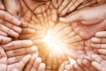 Photo of hands, palms up, in a circle with light shining through the middle