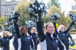 Photo of CWRU cheerleaders with pompoms held up during homecoming parade