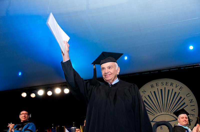 Photo of Morton Mandel holding up a diploma during commencement