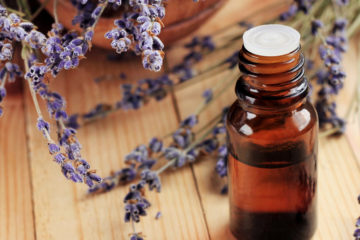 Photo of essential oils bottle on table next to lavender plant