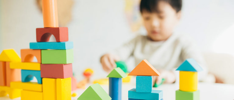 Photo of toy blocks stacked with a blurred boy playing with them in the background