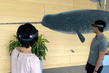 a composite photo of four students wearing HoloLens headsets and looking at an image of a narwhal swimming past them