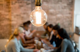 Employees brainstorming around a table under a lightbulb