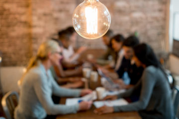 Photo with focus on a lightbulb hanging from ceiling and entrepreneurs gathering around a desk in the background