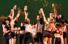 Photo of a group of dancers jumping in a circle while holding cups with confetti coming out