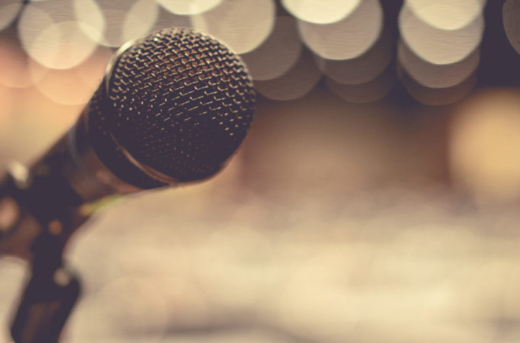 Photo with a focus on a microphone in front of a blurred background