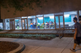 Photo of two blurred students walking on a campus path at night past a well-lit building with students at tables inside