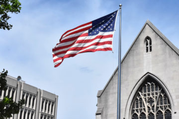 Photo of a flag waving in the wind in front of Amasa Stone Chapel