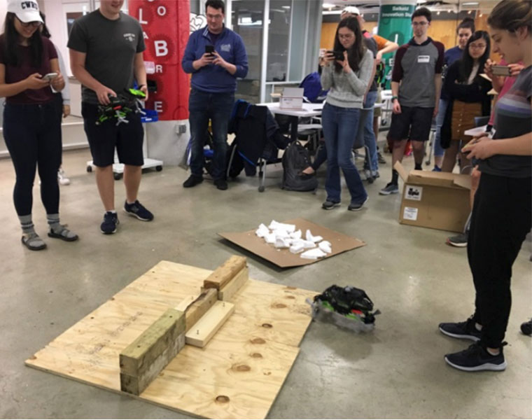 Case School of Engineering students stand around a small robotic vehicle and watch it try to climb over a block of wood