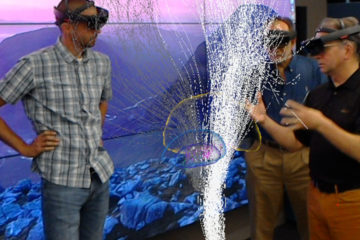 a team of scientists wearing holographic headsets views a 3D representation of a human brain