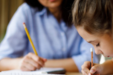 Young female student writing with a pencil learning from an interventionist
