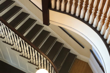 Photo looking down on a white and dark wood colored staircase with a curved landing above