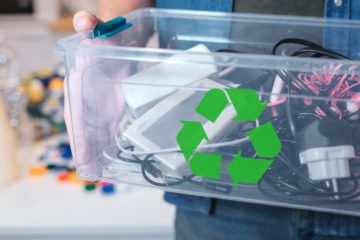 Close up photo of a person holding a bin with a recycle symbol on it and electronics in it