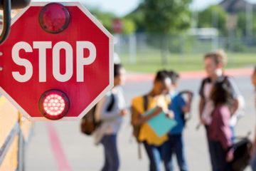 Photo of a bus with stop sign extended and a group of adolescents waiting next to it