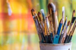 Photo of a cup of paintbrushes against a brightly painted background