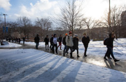 Photo of students walking along a campus path surrounded by snow on the ground