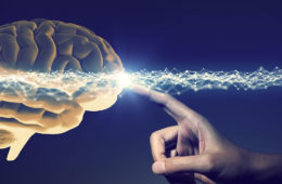 Photo illustration of a brain with a hand pointing and brain waves running across the image