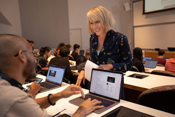 Photo of a faculty member talking and smiling at a student working on a laptop in lecture classroom